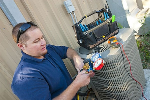 HVAC Technician Inspecting Air Conditioning Unit